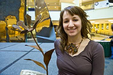 photo of an art student next to a sculpture