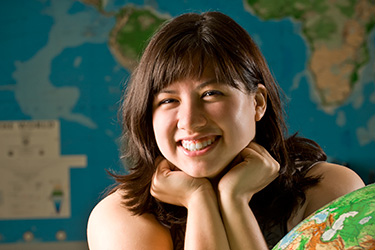 photo of a student in front of a world map