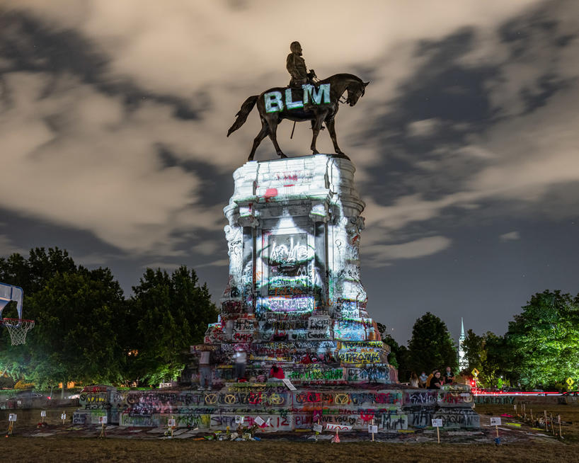 Artist photograph of Robert E. Lee equestrian monument covered in graffiti and projection of George Floyd