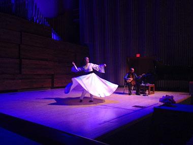 Woman in long dress dancing to guitar music at Sufi dance event