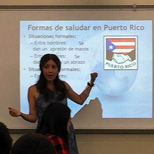 Spanish professor presenting slide about Puerto Rico in front of high school classroom